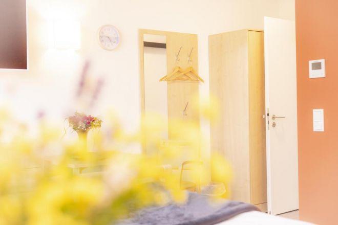 Schlafraum mit Blumen bei Hospiz zum guten Hirten